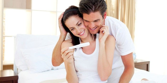 Женщина с мужчиной смотрят на тест на беременность