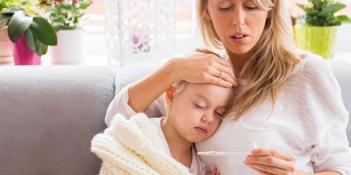 Женщина с ребенком смотрит на градусник