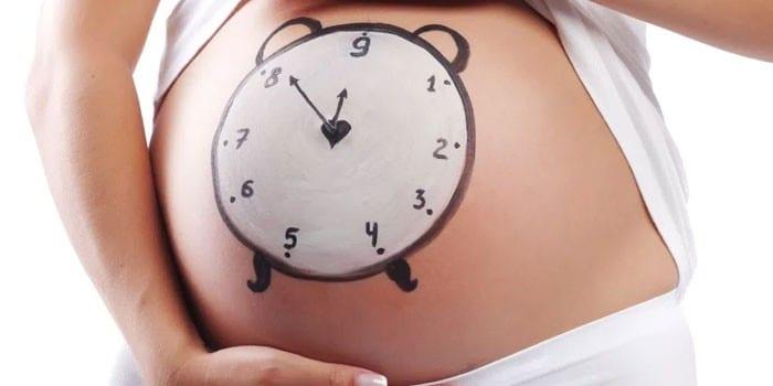 Нарисованные часы на животе беременной женщины