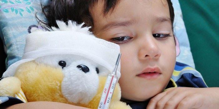 Мальчик лежит в постели с мягкой игрушкой и градусником