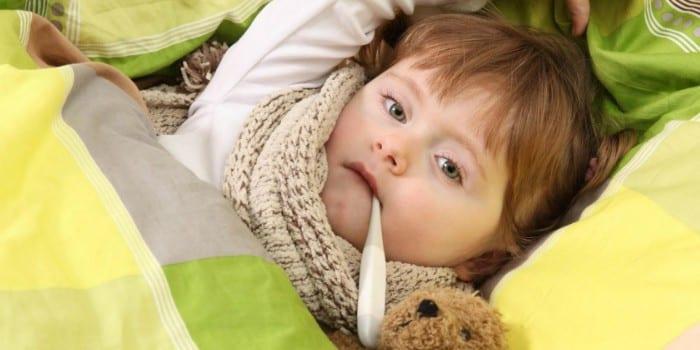 Ребенок в кровати с градусником