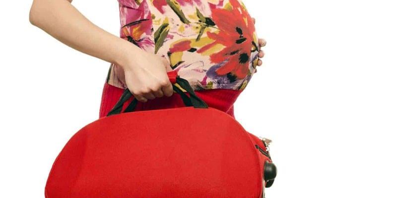 Беременная девушка с дорожной сумкой