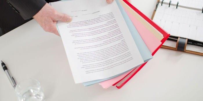 Мужчина держит в руках папку с документами