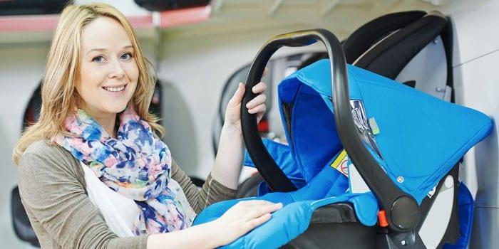 Девушка с детской автолюлькой в руках