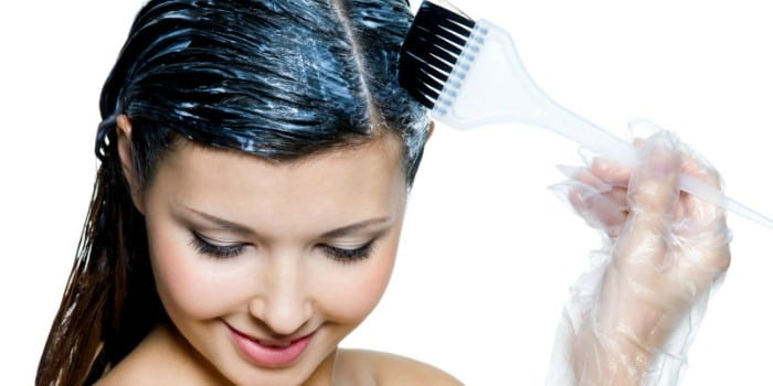 Девушка наносит краску на волосы