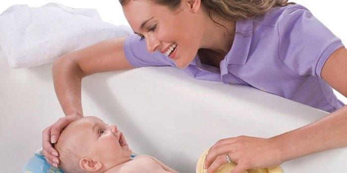 Девушка купает ребенка