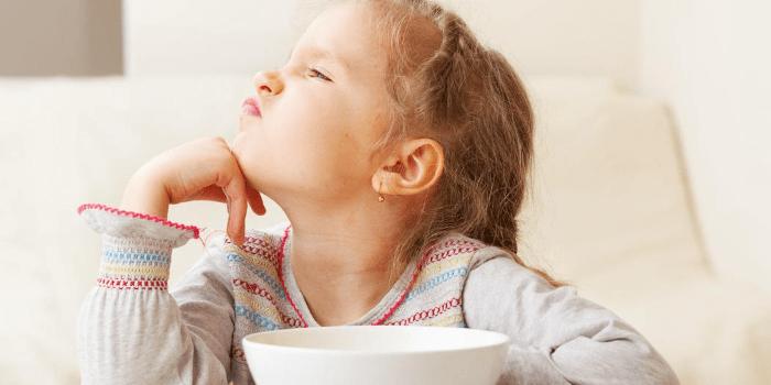 Девочка отвернулась от тарелки с едой