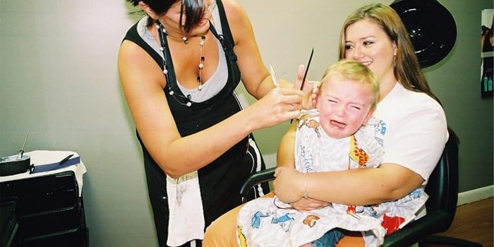 Девочка плачет во время стрижки