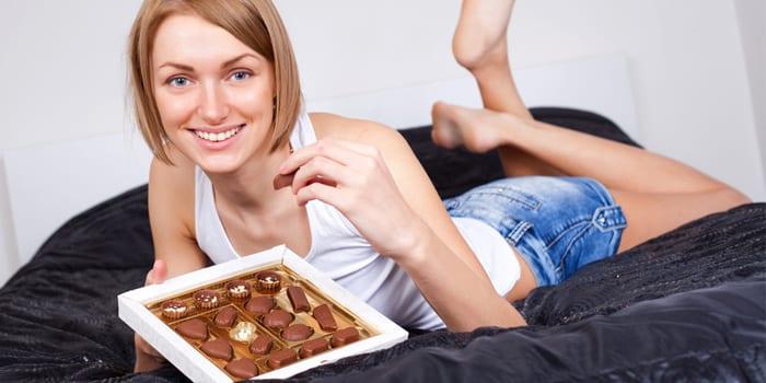 Девушка ест конфеты