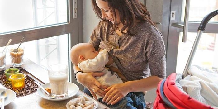 Женщина кормит грудничка грудь