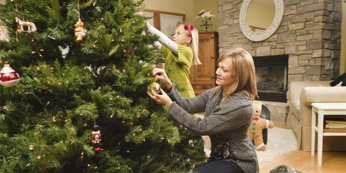 Девочка и мама украшают натуральную ель