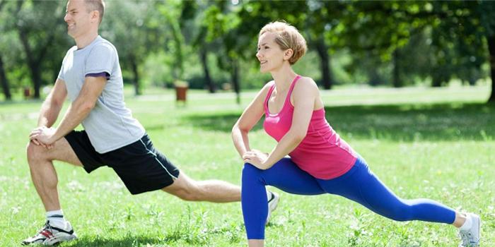 Мужчина и женщина занимаются физкультурой на природе