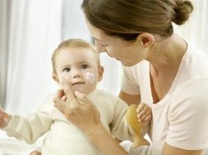 Мама наносит крем на щечки малыша