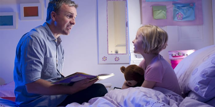Папа читает книжку дочке перед сном