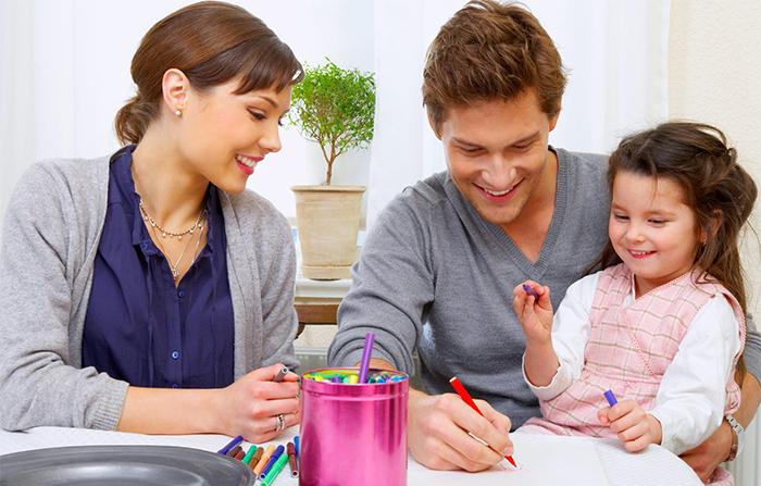 Девочка рисует вместе с родителями